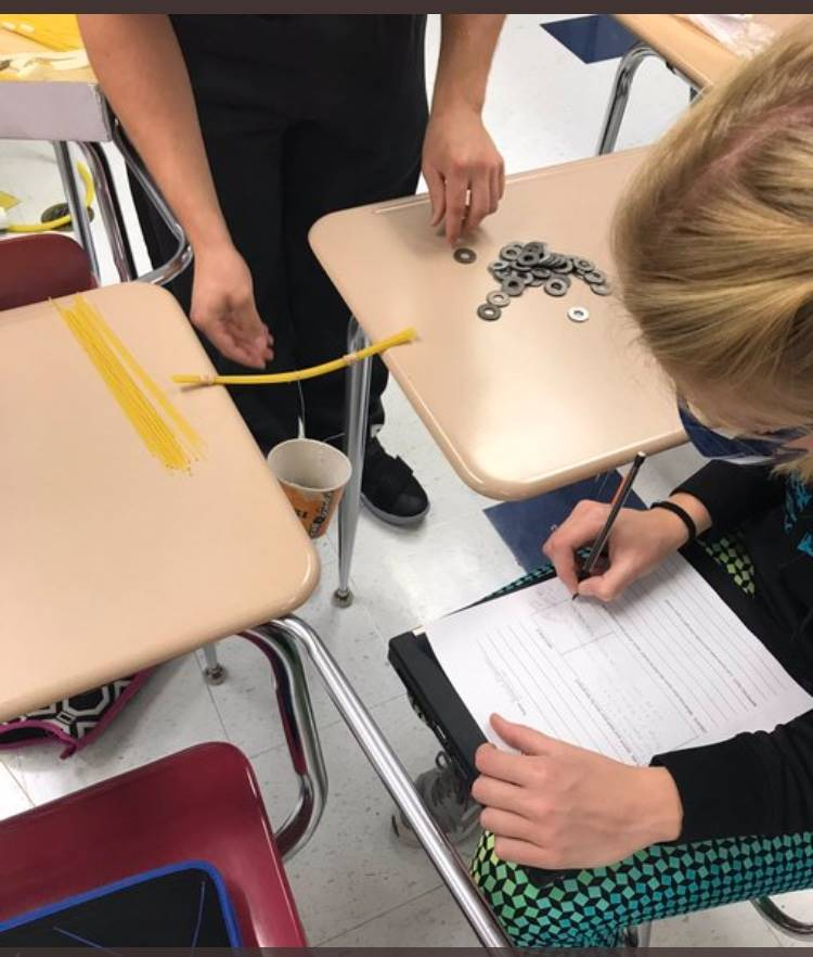 Students working with spaghetti noodles and washers