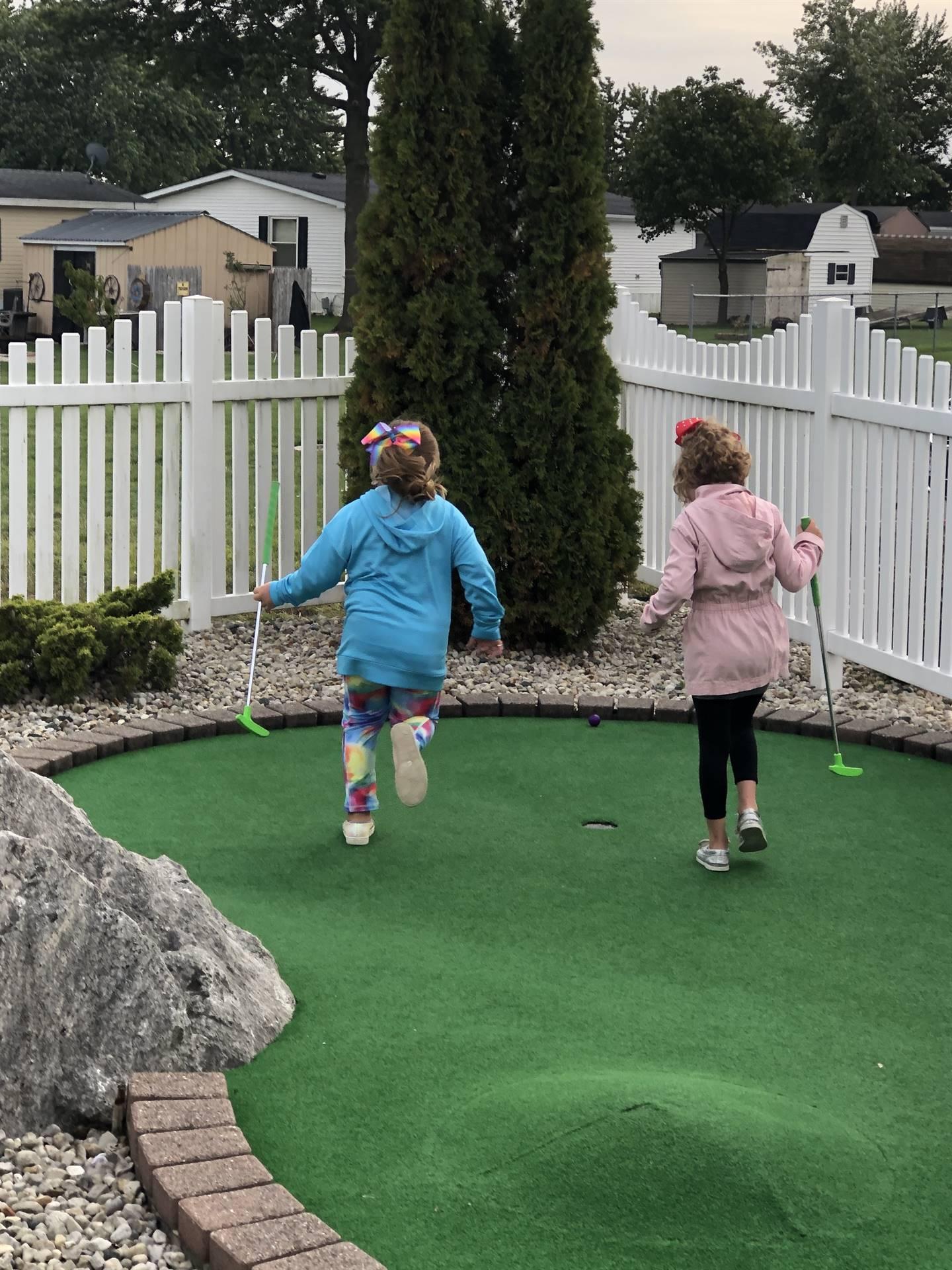 Two girls playing putt putt golf
