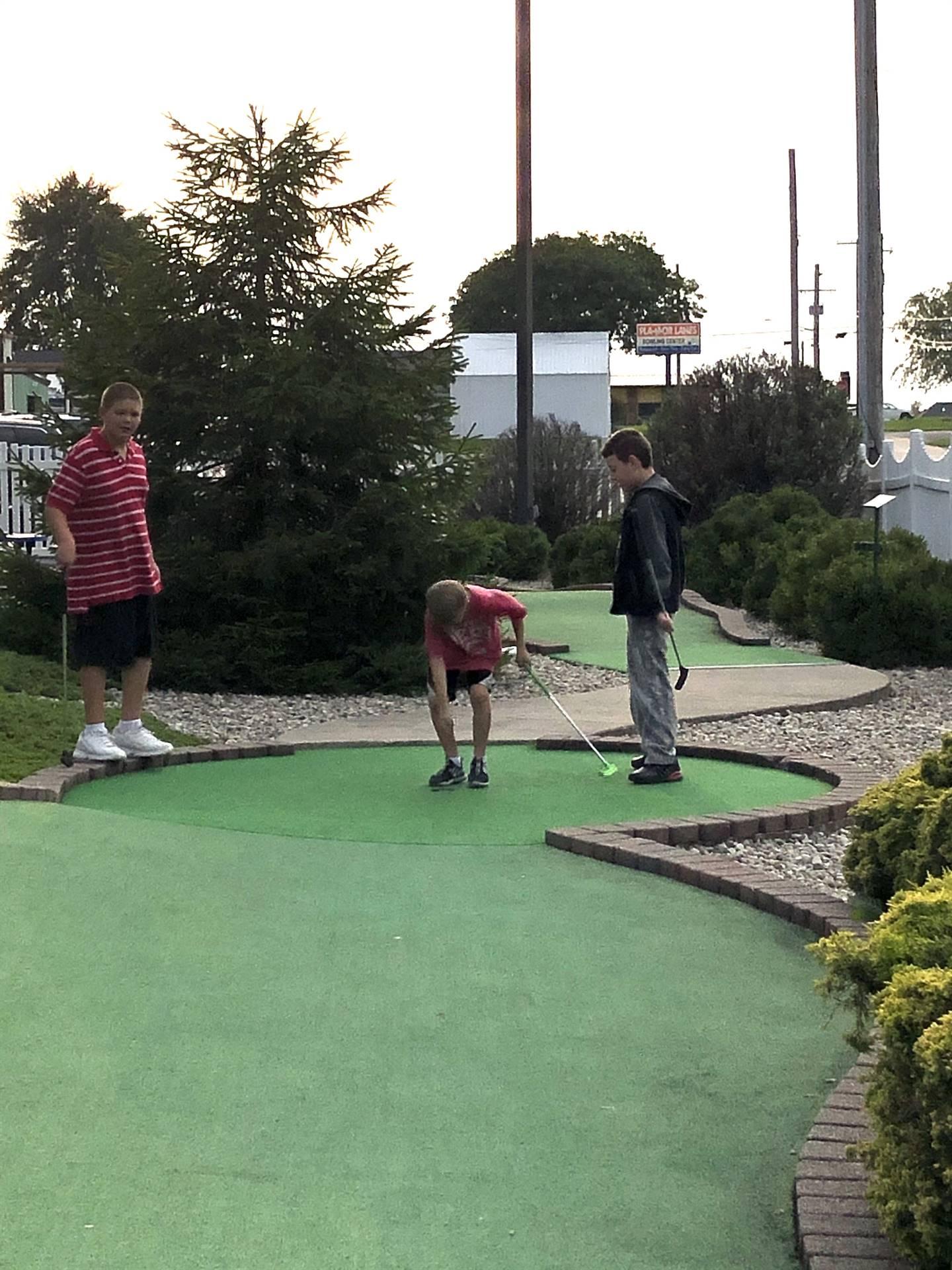 Playing putt putt golf.